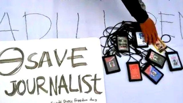 Sebuah tulisan dan ID Card Jurnalis diletakan di atas sebuah spanduk, tanda protes terhadap kriminalisasi jurnalis. (Ist/Int)