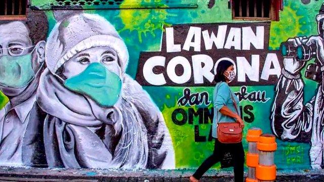 Seseorang yang berjalan di depan sebuah tembok yang berisi lukisan sebagai tanda bahwa tenaga kesehatan mengajak semua masyarakat Indonesia untuk lawan virus corona. FOTO: Istimewa.