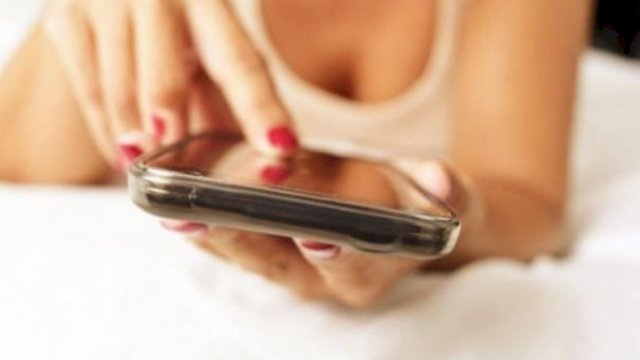 Seseorang yang berpakaian cukup terbuka sambil menggengam smartphone (foto ilustrasi).