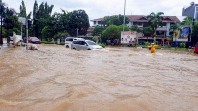 Kendaraan saat melintasi jalan yang tergenang banjir di kawasan Puri Indah, Kembangan, Jakarta Barat, Sabtu (20/2/2021). | AKURAT.CO/Sopian