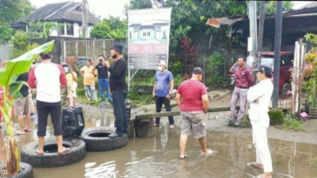 FOTO: Diduga Kesal karena Selalu Tergenang Air, Warga Kota Makassar Blokir Lalin dan Tanam Pisang di Tengah Jalan
